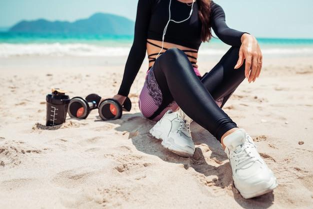 Ciérrese encima de la foto de una mujer delgada en aptitud de la ropa negra que se sienta en la arena con pesas de gimnasia, botella de agua. deporte. vacaciones de verano
