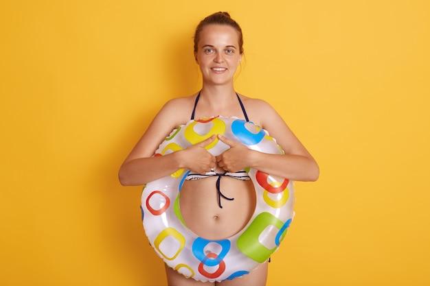 Ciérrese encima de la foto de la persona divertida alegre alegre que sostiene al salvavidas en la pared amarilla aislada de las manos, hembra sonriente, no puede nadar, utiliza el anillo de goma.