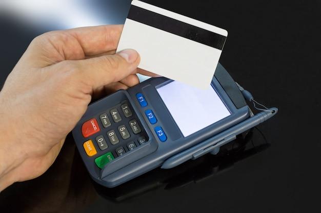 Ciérrese encima de la foto de un terminal del pago que carga de una tarjeta.