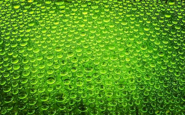 Ciérrese encima de la gota del agua del color en el vidrio para el fondo