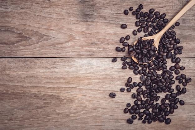 Ciérrese encima de los granos de café en cuchara de madera en la opinión de sobremesa de madera