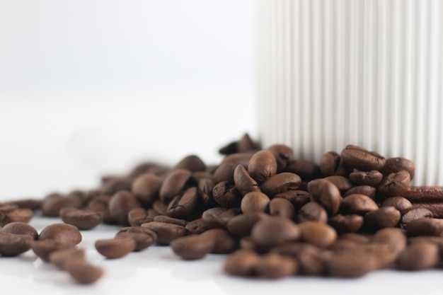 Ciérrese encima de los granos de café y de la taza blanca aislados en el fondo blanco.