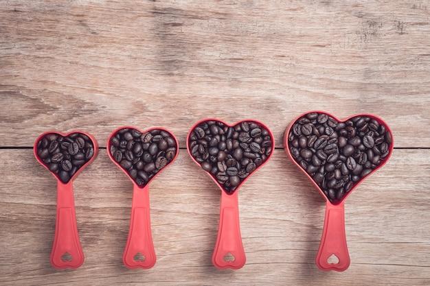 Ciérrese encima de los granos de café en taza plástica del corazón rojo en la opinión de sobremesa de madera