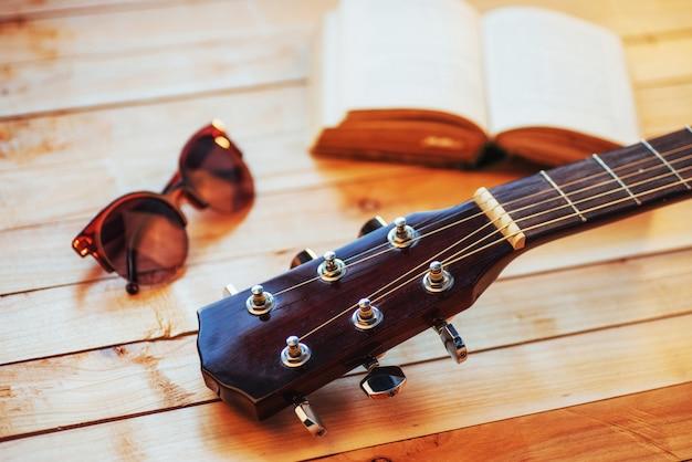 Ciérrese encima de la guitarra clásica acústica del cuello en un fondo de madera claro