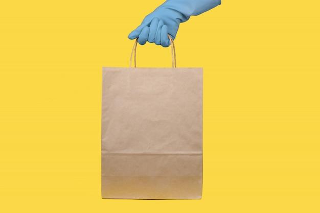 Ciérrese encima de la hembra sostiene la bolsa de papel en blanco vacía clara en blanco marrón del arte para llevar aislada concepto del servicio de entrega. copia espacio área de publicidad
