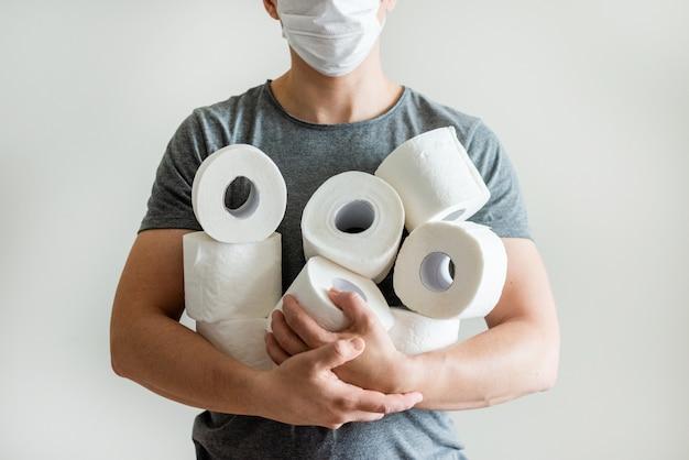 Ciérrese encima de hombre con el fondo de los rollos del papel higiénico. concepto de falta de papel higiénico en las tiendas debido a covid-19, coronavirus, higiene, pánico.