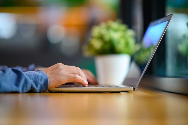 Ciérrese encima del hombre de negocios de manos que pulsan la tabla de madera del teclado del ordenador portátil en oficina.