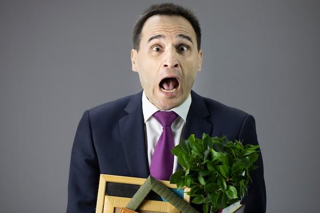 Ciérrese encima del hombre de negocios sorprendido de la edad media que sostiene la caja con sus cosas. despido