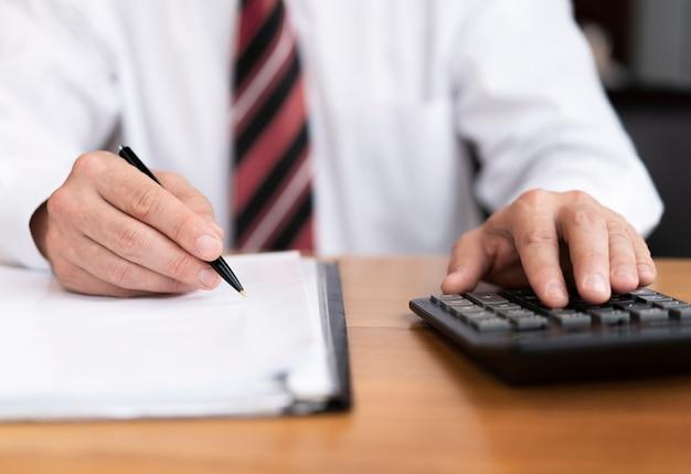Ciérrese encima del hombre de negocios usando la calculadora