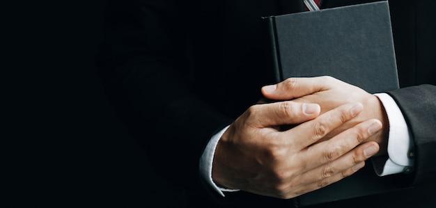 Ciérrese encima del hombre que sostiene un libro, muestra una mano del primer y un libro.