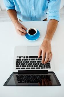 Ciérrese encima de la imagen de las manos del hombre de negocios joven que se sientan en la tabla que pulsa en la computadora portátil que sostiene la taza de café. interior de oficina moderno blanco