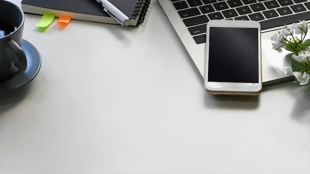 Ciérrese encima de la imagen de la mesa de trabajo blanca con los accesorios que la ponen ordenador portátil.