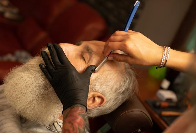 Ciérrese encima de la imagen del peluquero que afeita a un hombre con una cuchilla de afeitar de acero afilada. tiro macro
