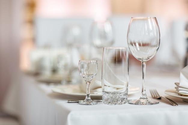 Ciérrese encima de la imagen de vidrios vacíos en restaurante. enfoque selectivo. vasos vacíos sobre la mesa