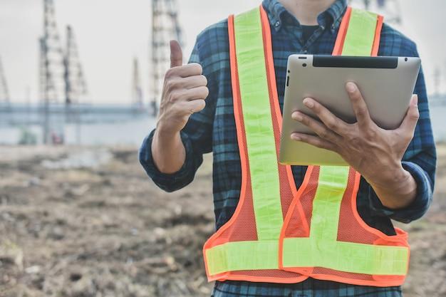 Ciérrese encima de la ingeniería de la construcción que sostiene la construcción del estado de la tableta