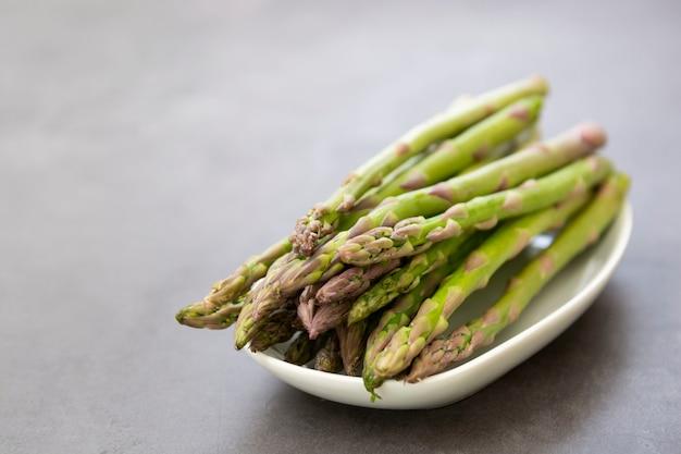 Ciérrese encima de las lanzas del espárrago sobre fondo oscuro con el espacio de la copia. concepto de comida sana y vegana. comer limpio.