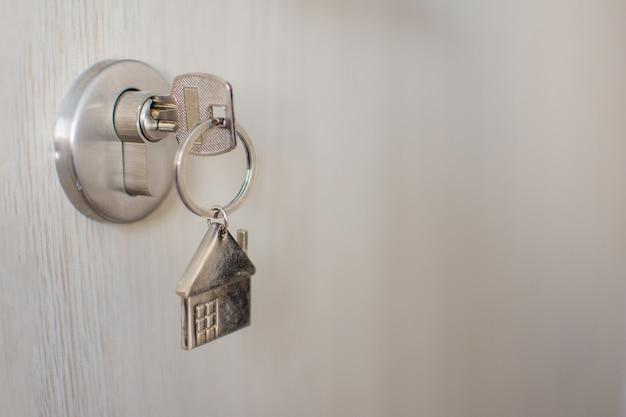 Ciérrese encima de la llave en la puerta con la luz de la mañana, préstamo personal. el sujeto está borroso.