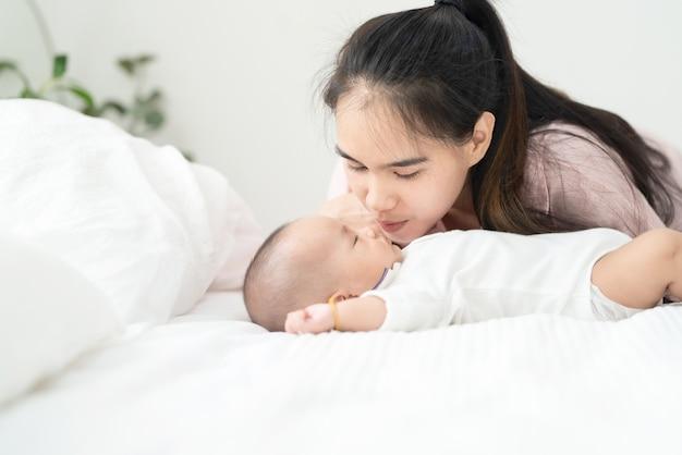 Ciérrese encima de la madre asiática joven hermosa que besa al bebé recién nacido en cama. asistencia sanitaria y médica. chica asiática amor estilo de vida.