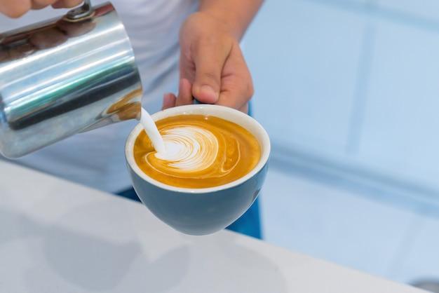 Ciérrese encima de la mano del barista que hace una taza de café.