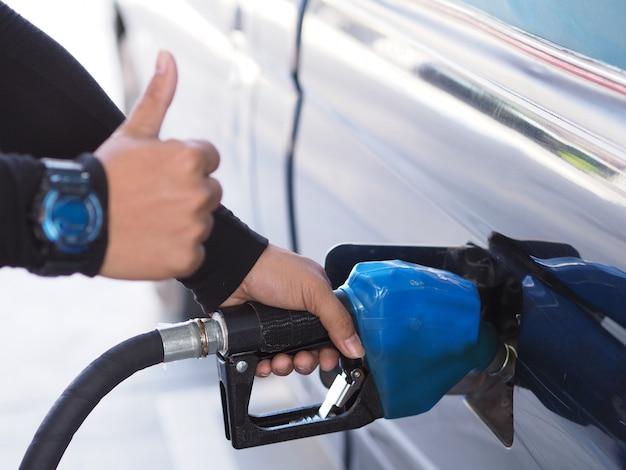 Ciérrese encima de la mano del combustible de bombeo de la gasolina del hombre en coche en la gasolinera.