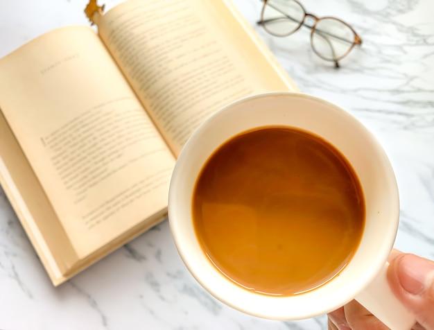 Ciérrese encima de la mano derecha que sostiene una taza de café