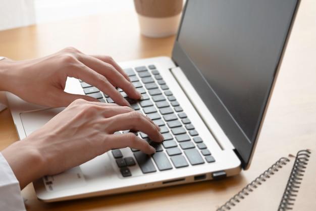 Ciérrese encima de la mano de la empresaria que pulsa en el teclado de la computadora portátil.