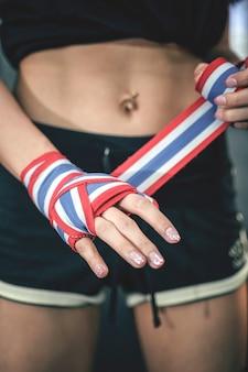 Ciérrese encima de la mano femenina del combatiente usando los pañuelos