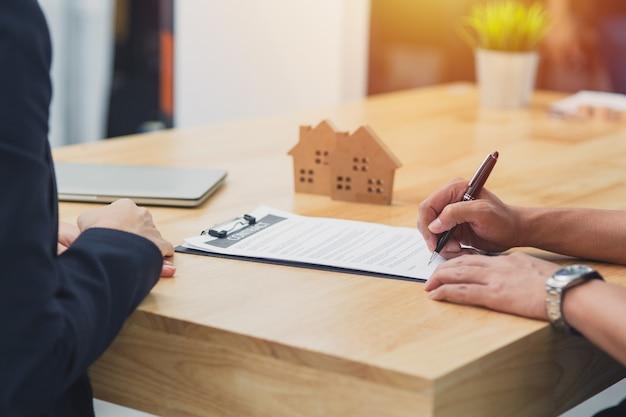 Ciérrese encima de la mano firme la firma al papel del contrato de la casa con la agencia inmobiliaria de la venta de la casa