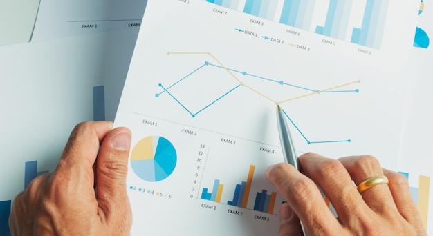 Ciérrese encima de la mano del hombre de negocios con análisis de contabilidad del informe financiero.