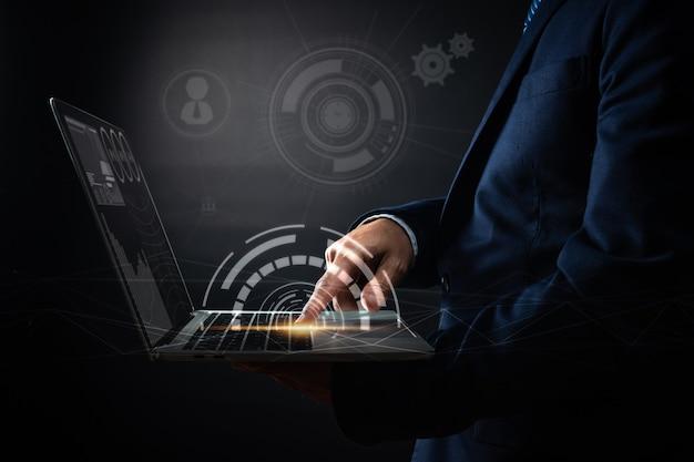 Ciérrese encima de la mano del hombre de negocios presione en la computadora portátil y utilice las compras en línea modernas de la interfaz