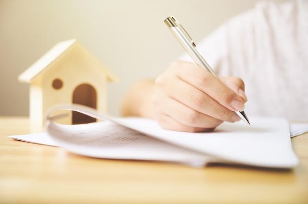 Ciérrese encima de la mano del hombre que firma el documento del préstamo de la firma a la propiedad de la vivienda.