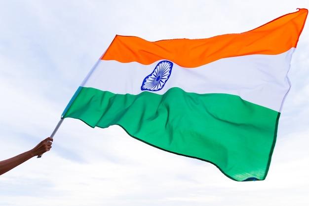 Ciérrese encima de la mano del hombre que sostiene la bandera de la india en el fondo del cielo azul.