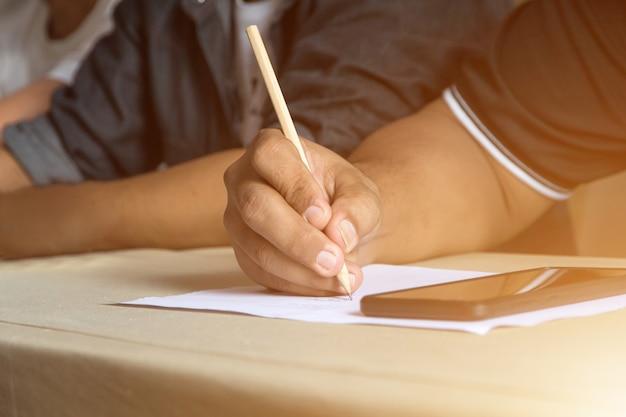 Ciérrese encima de la mano del hombre usando el lápiz para escribir en la hoja entre la reunión en el cuarto