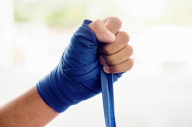 Ciérrese encima de la mano masculina del boxeador con los vendajes azules del boxeo.