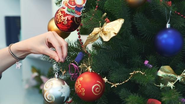 Ciérrese encima de la mano de la mujer que cuelga los juguetes en el árbol de navidad