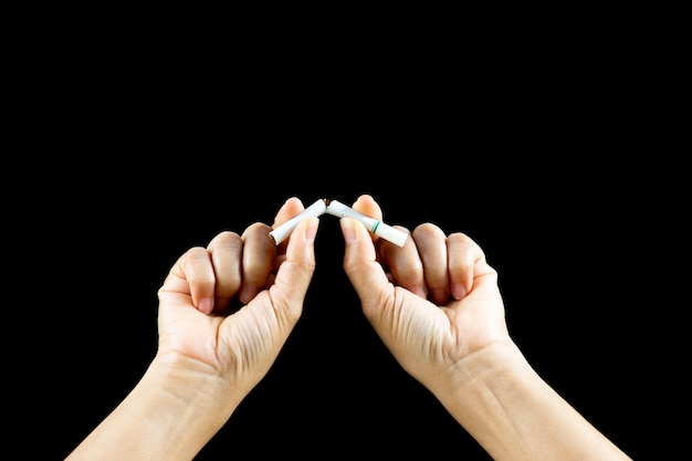 Ciérrese encima de la mano de la mujer que rompe, machacando o destruyendo los cigarrillos en fondo negro.