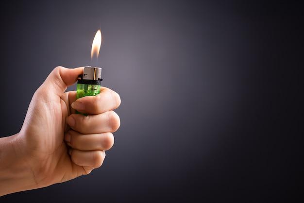 Ciérrese encima de la mano de la mujer que sostiene un mechero ardiente en la oscuridad.
