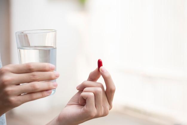 Ciérrese encima de la mano de la mujer que sostiene la píldora roja y el vaso de agua