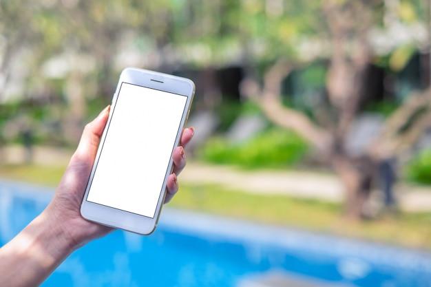 Ciérrese encima de la mano de la mujer que sostiene el teléfono blanco en la pantalla en blanco en el parque al aire libre