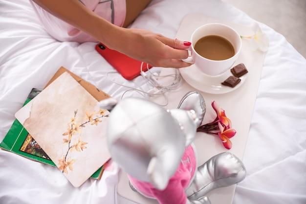 Ciérrese encima de una mano de la mujer con la taza de café y un plato con pedazos de cama de chocolate con leche. buenos dias