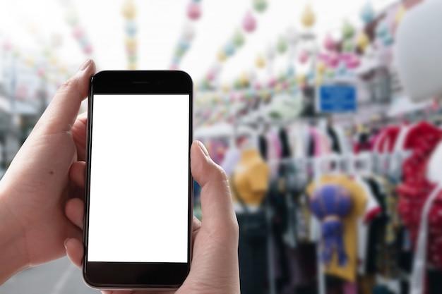 Ciérrese encima de la mano de la mujer usando un teléfono elegante con la pantalla en blanco en el mercado.