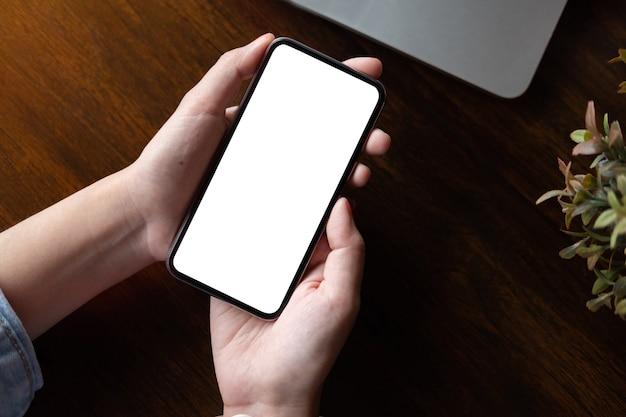 Ciérrese encima de la mano de la mujer usando un teléfono elegante con la pantalla en blanco en la oficina.