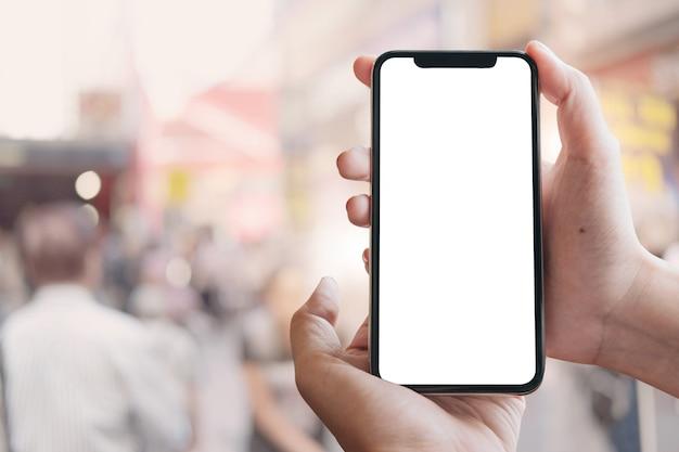 Ciérrese encima de la mano de la mujer usando un teléfono inteligente con la pantalla en blanco en el maket.