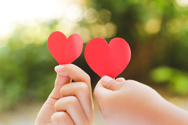 Ciérrese encima de la mano de los niños que llevan a cabo mini corazón en fondo verde.