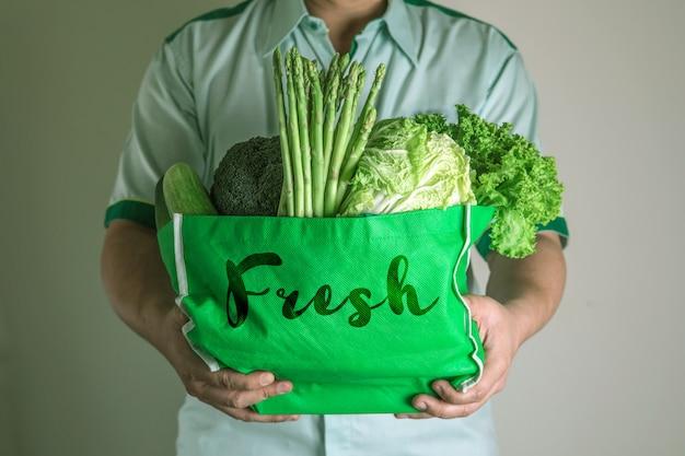 Ciérrese encima de la mano que sostiene la bolsa de supermercado verde de las verduras verdes orgánicas mezcladas, compras orgánicas sanas de la comida verde y terapia de la nutrición de la atención sanitaria de la dieta