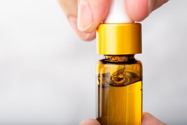 Ciérrese encima de la mano que sostiene la botella de aceite de cannabis aceite de cbd de marihuana