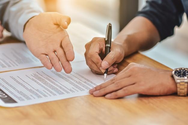 Ciérrese encima de la mano que sostiene el contrato de la muestra de la pluma en el documento