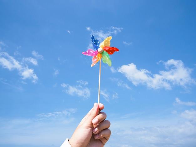 Ciérrese encima de la mano que sostiene el molinillo de viento colorido sobre fondo del cielo azul.