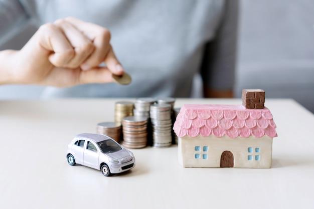 Ciérrese encima de la mano que sostiene la moneda, la pila de dinero, la casa del juguete y el coche en la tabla, ahorrando para el futuro, maneje al éxito, concepto de las finanzas.