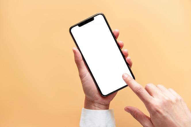 Ciérrese encima de la mano que sostiene la pantalla blanca negra del teléfono inteligente